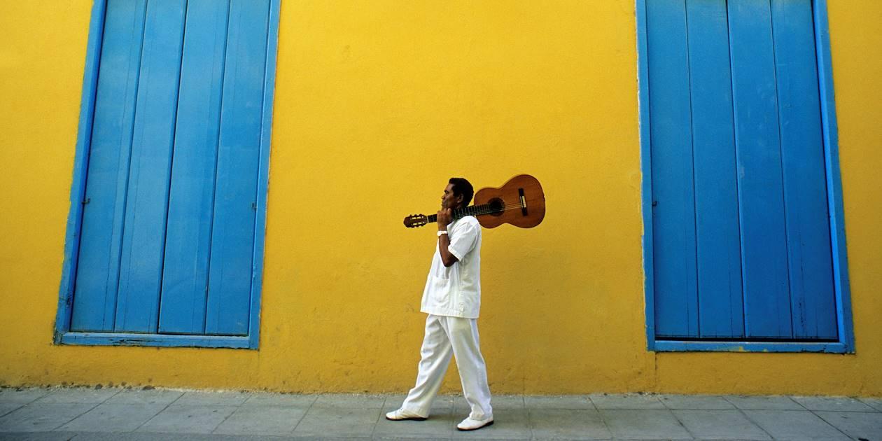 Portrait de musicien portant une guitare sur fond de façade coloniale - La Havane - Cuba