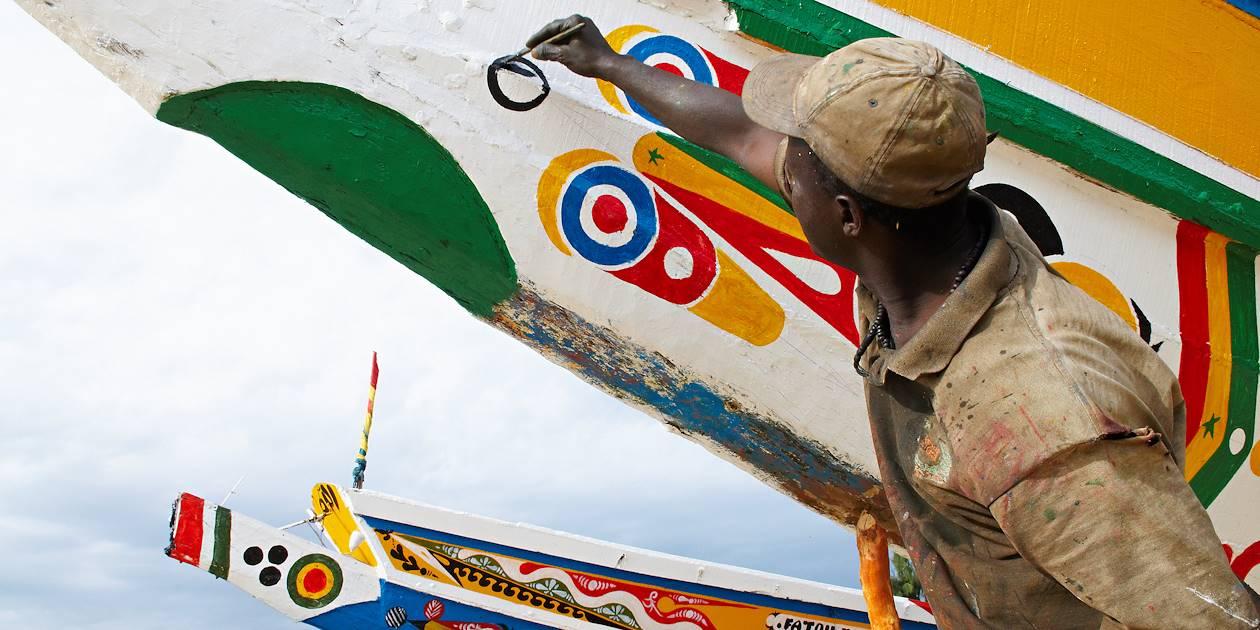 Homme peignant la coque d'un bateau - Mbour - Région de Thiès - Sénégal