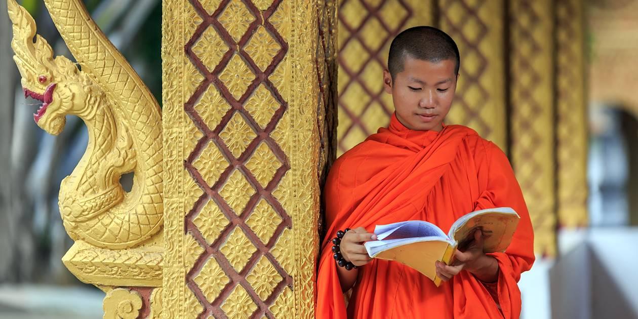 Moine bouddhiste lisant un livre de prière - Laos