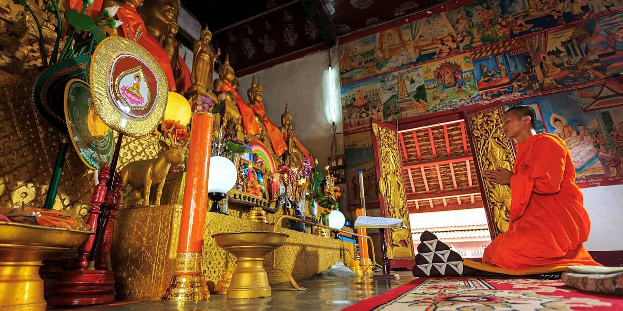 Moine priant à l'intérieur d'un temple - Laos