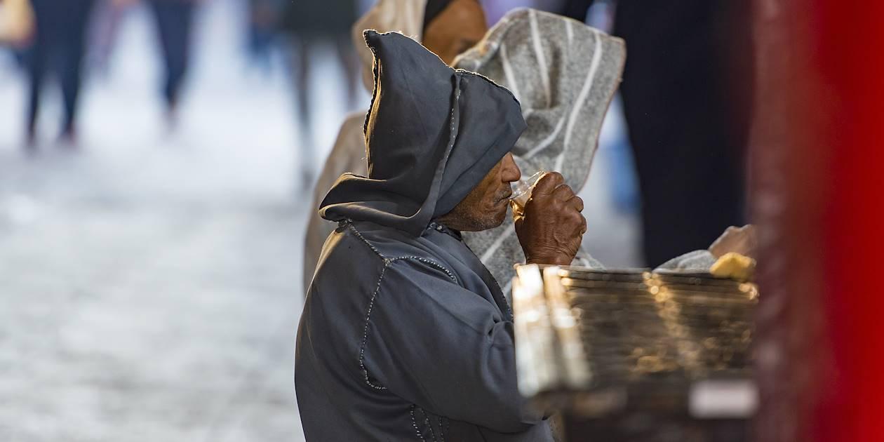 Homme en tenue traditionnelle buvant un thé dans la rue - Maroc