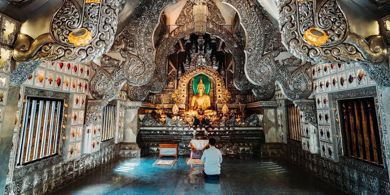 Homme priant à l'intérieur du Temple Wat Sri Suphan, ou le Temple d'Argent - Chiang Mai - Thaïlande