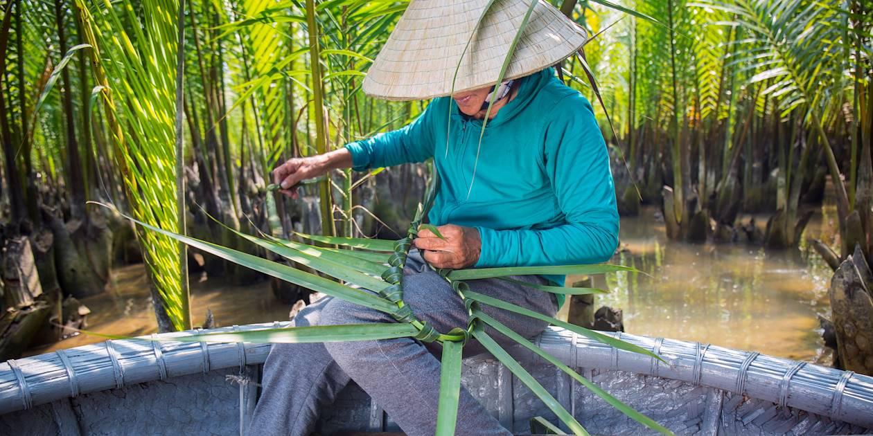 Tressage de feuilles de palmier dans la mangrove - Vietnam