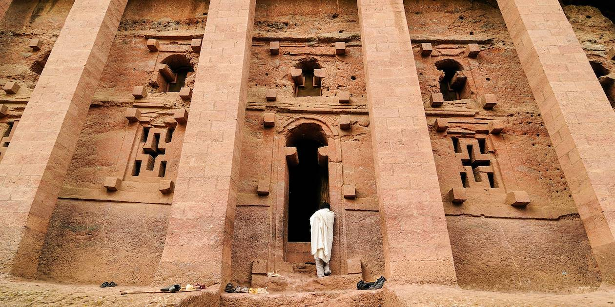 Ethiopien orthodoxe face à une église rupestre de Lalibela - Éthiopie