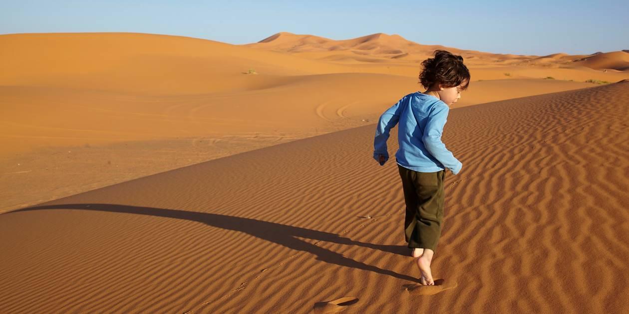 Enfant courant dans les dunes de Merzouga - Maroc