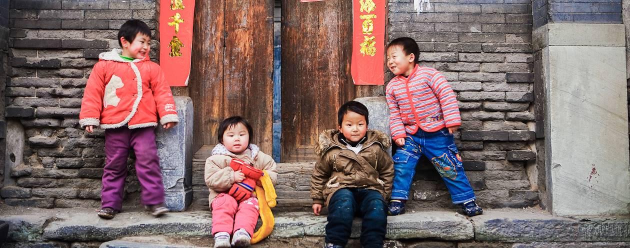 Enfants jouant devant une maison traditionnelle d'un hutong - Pékin - Chine