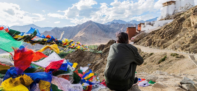 Femme assise près des drapeaux de prières tibétains - Ladakh - Inde