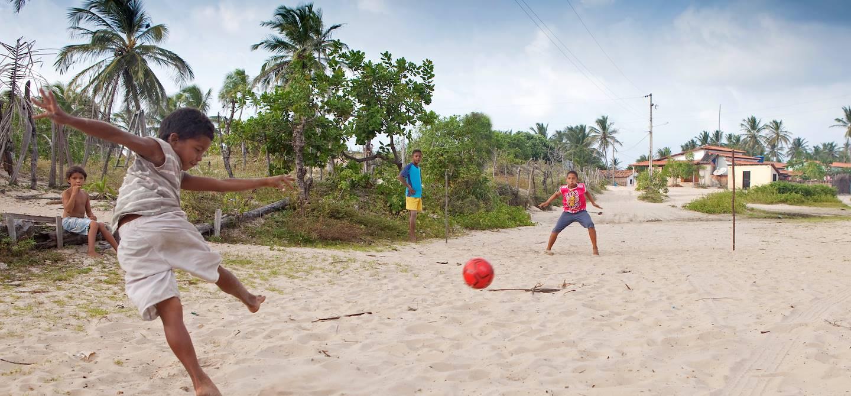 Enfant jouant au football dans le Parc National des Lencois Maranhenses - Atins - Brésil