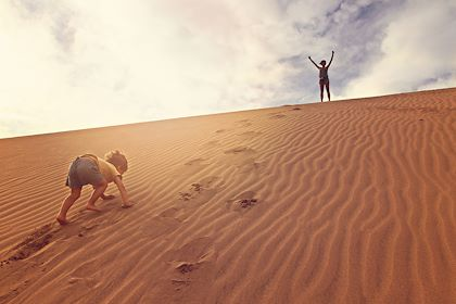 Enfant grimpant une dune de sable - Sashkalenka/stock.adobe.com