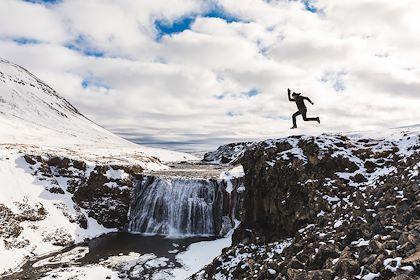 Homme sautant près d'une cascade - Islande - william87/stock.adobe.com