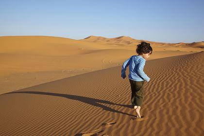 Enfant courant dans les dunes de Merzouga - Maroc - Blend images/hemis.fr