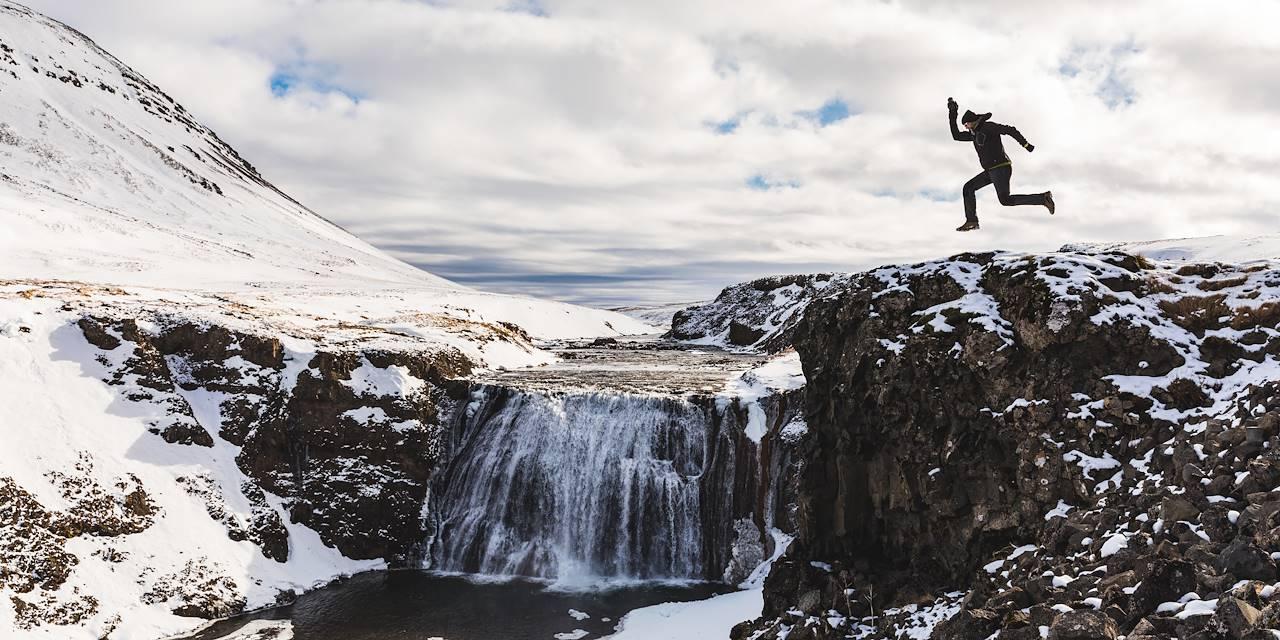Homme sautant près d'une cascade - Islande